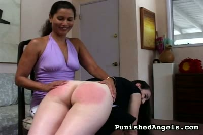 Natalie0. A young woman lies across the knees of another woman, who administers a relatively gentle spanking to her upper thighs, then removes the young woman's panties and has at her bare buns.
